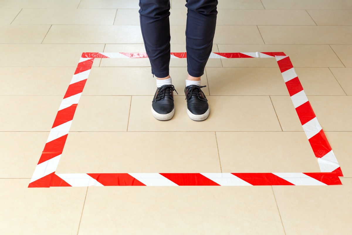 person standing in masking tape square on floor as social distancing measure in store