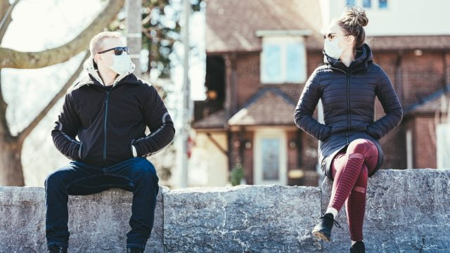 Young couple wearing disposable face masks meeting in outdoors. Mask is Disposable Earloop Face Mask with Filters against Bacteria.