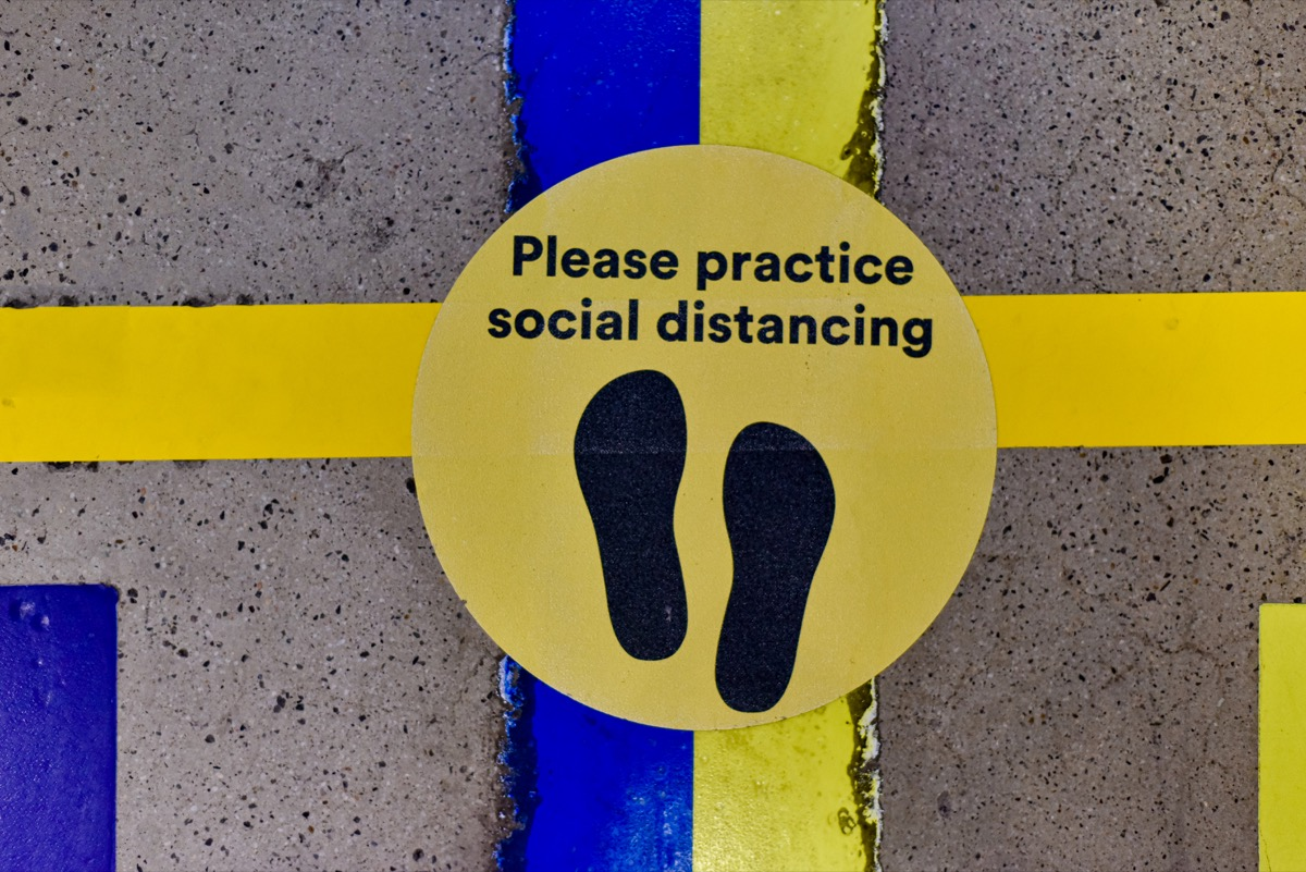 A placeholder label on the ground to reminder shoppers to practice social distancing