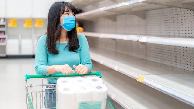 woman looking at Supermarket empty toilet paper shelves amid COVID-19 coronavirus fears, shoppers panic buying and stockpiling toilet paper preparing for a pandemic.