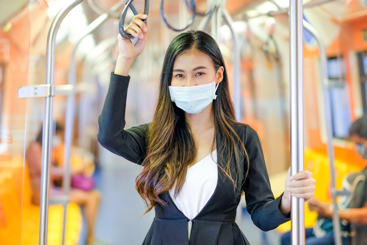 Woman holding subway pole
