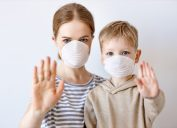 Adult woman and little boy in medical masks showing stop gesture and looking at camera during coronavirus epidemic against gray background