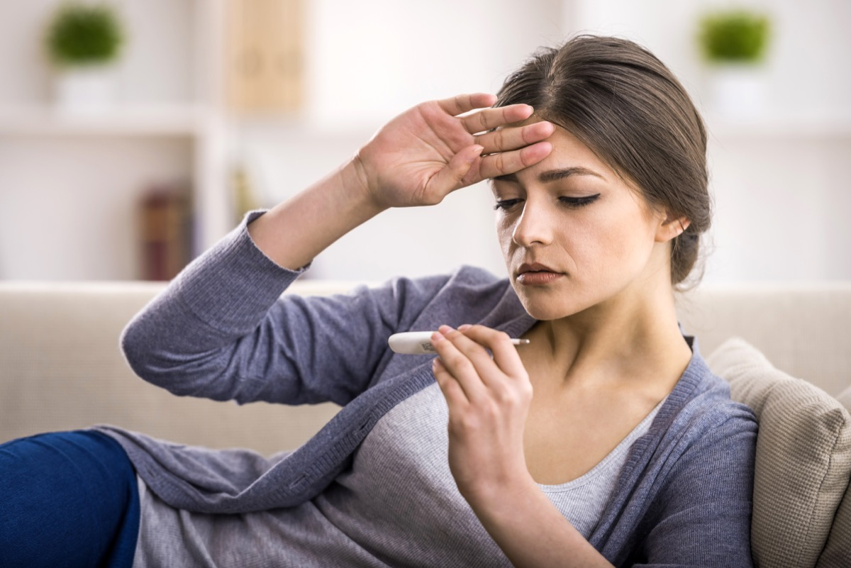 Woman taking her temperature to check for a fever