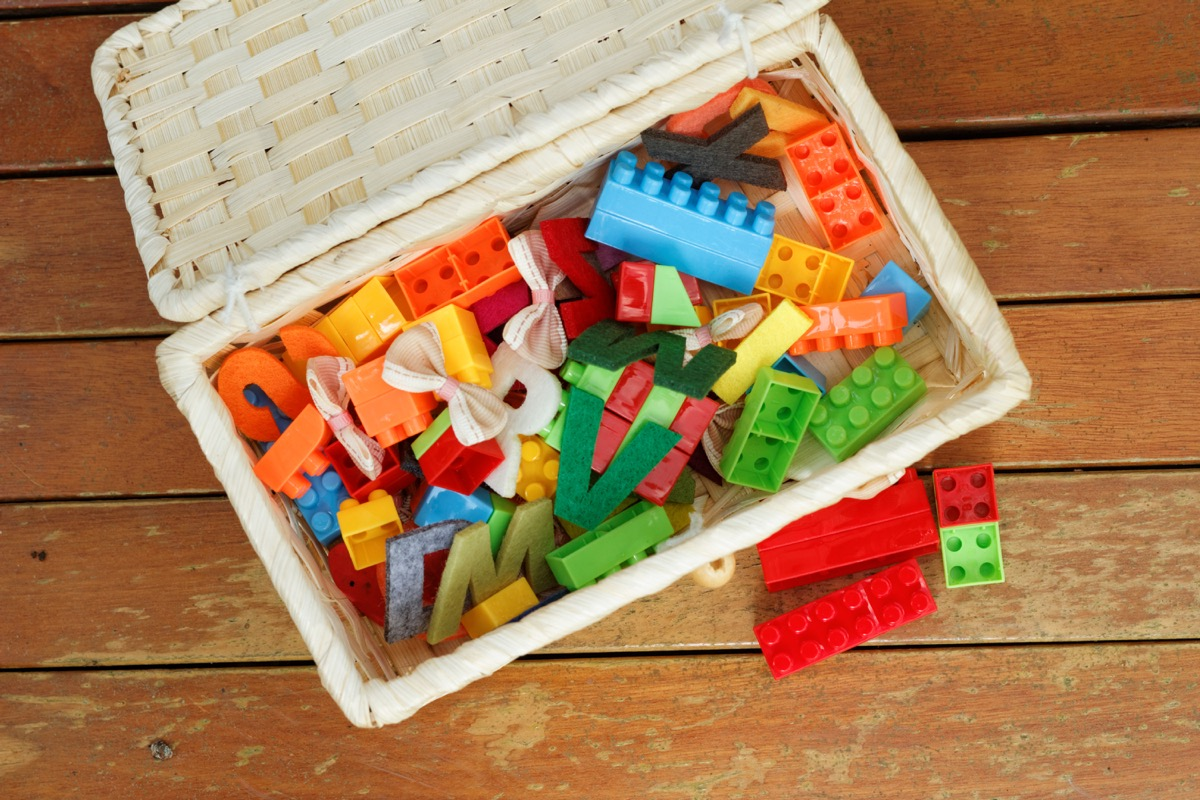 wicker toy box full of legos and toys