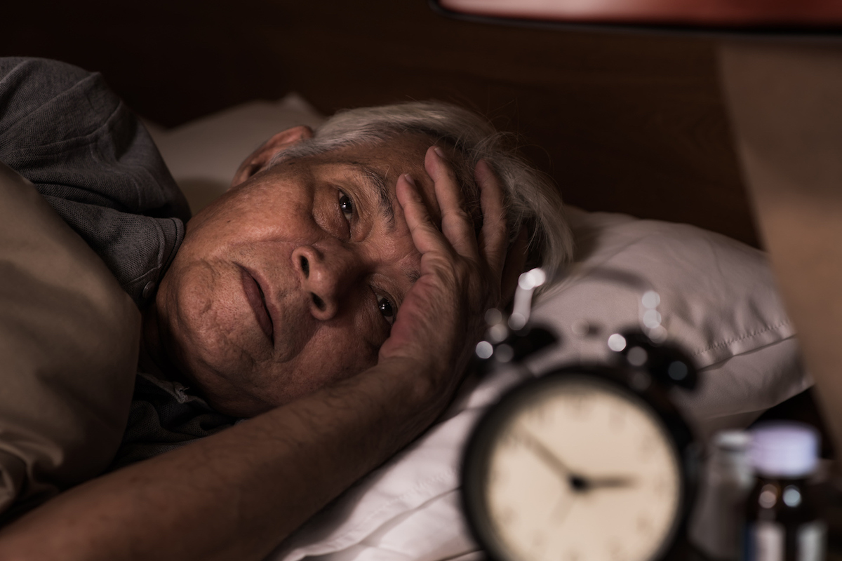 Asian senior man lying in bed but cannot sleep from insomnia