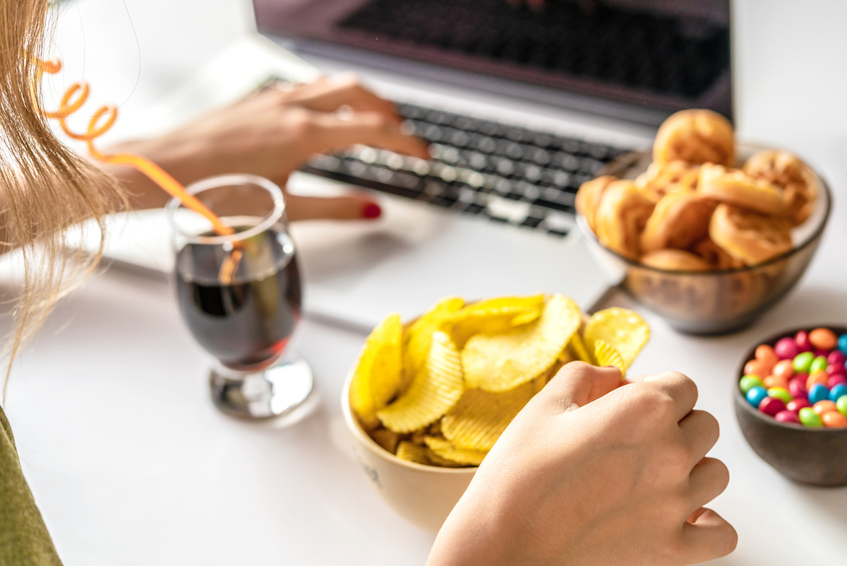 woman works at a computer and eats unhealthy food: chips, crackers, candy, waffles, soda