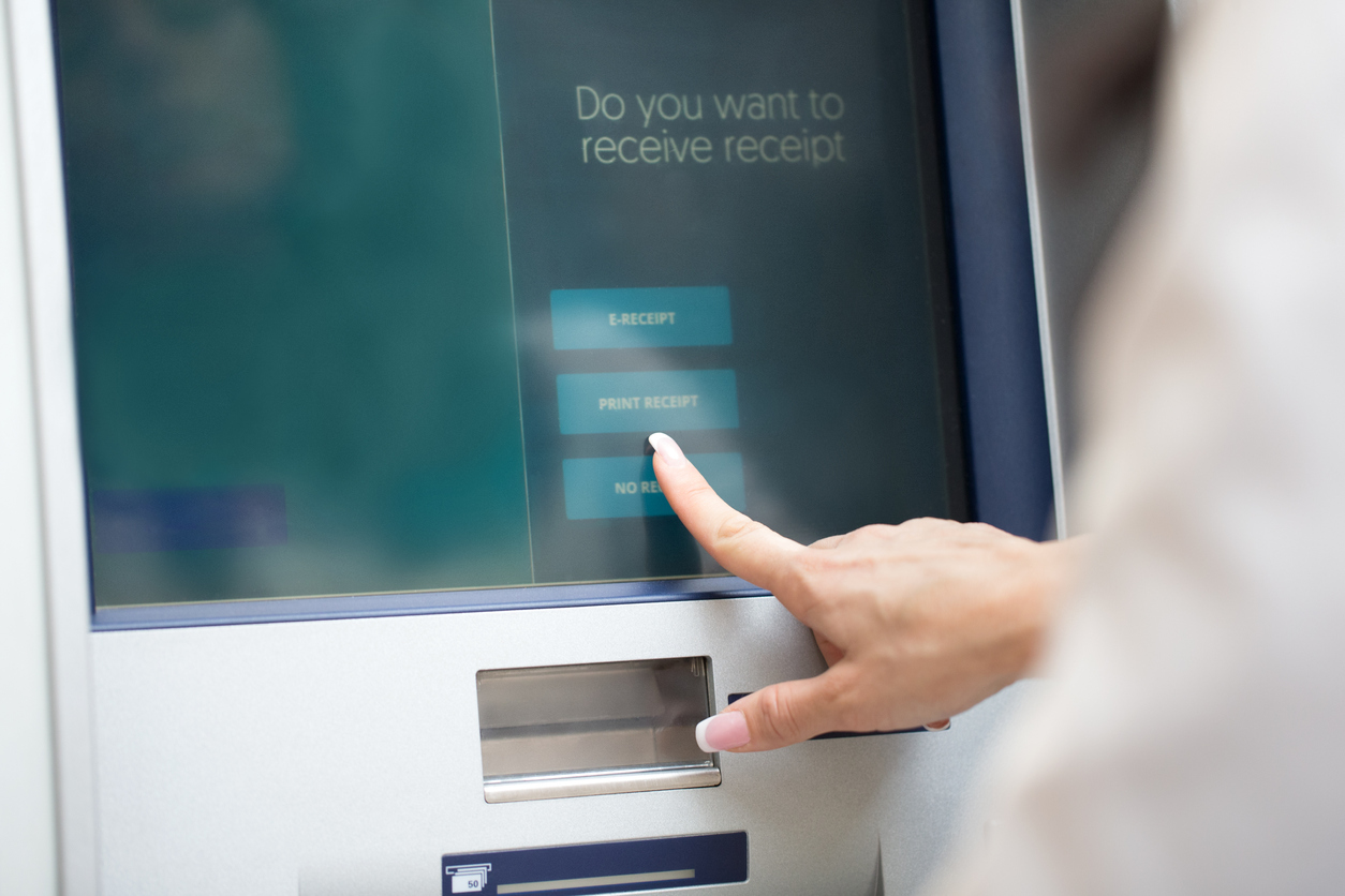 A woman pressing on an atm touch screen to receive a receipt