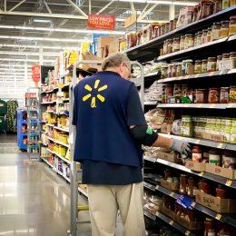 older male walmart employee stocking shelves
