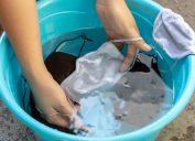 hands washing cloth masks in bucket