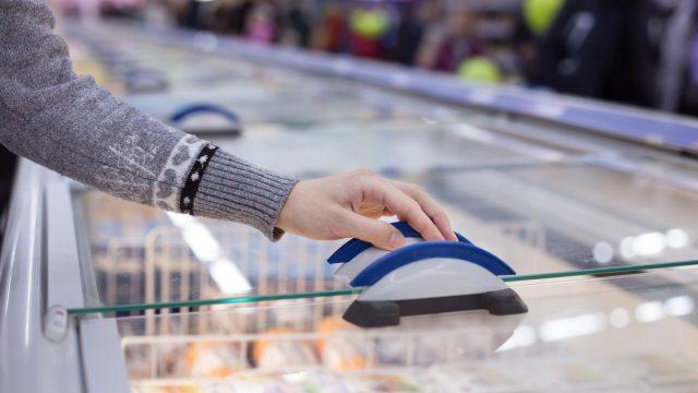 hand opening freezer case in supermarket