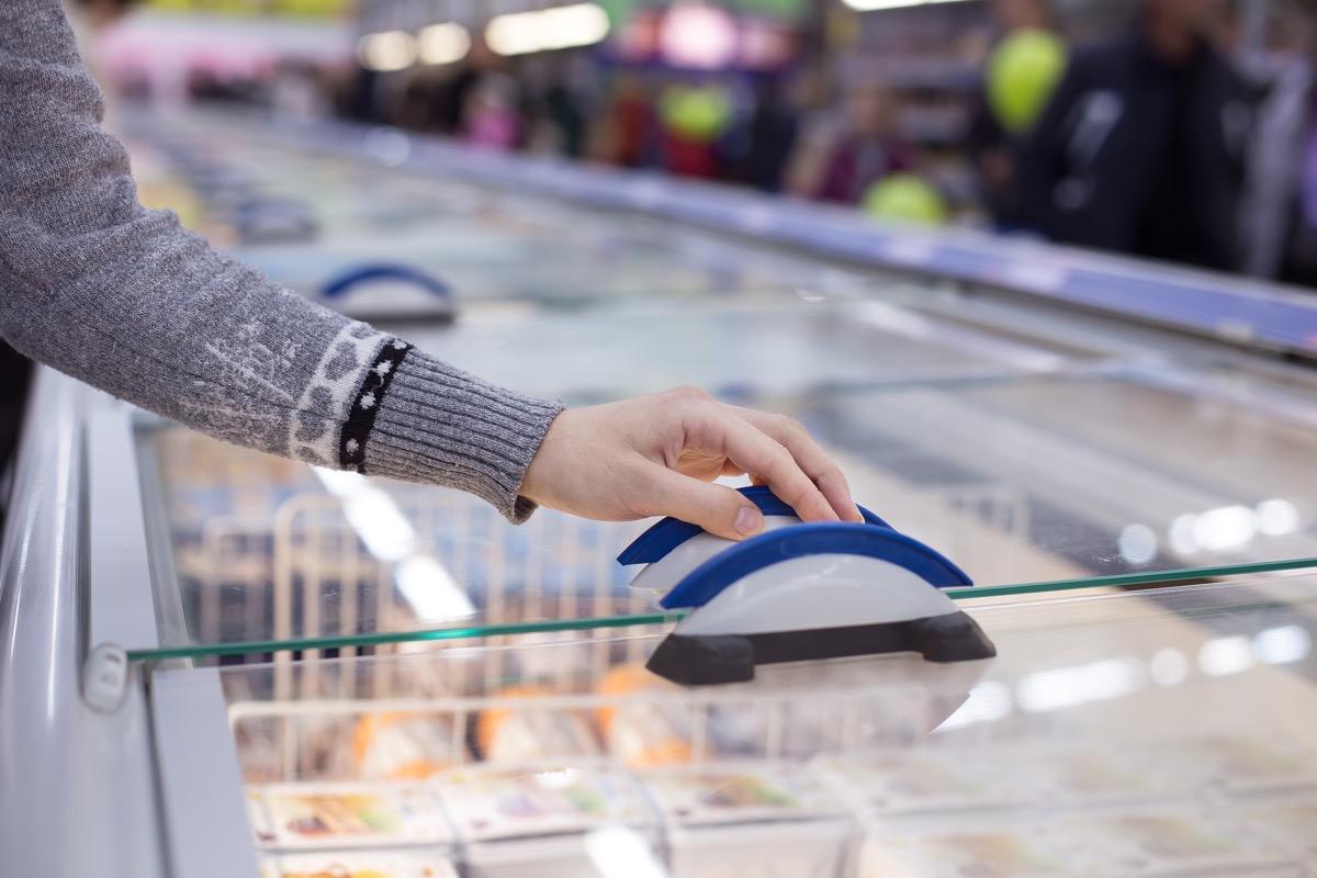 white hand opening freezer case in supermarket