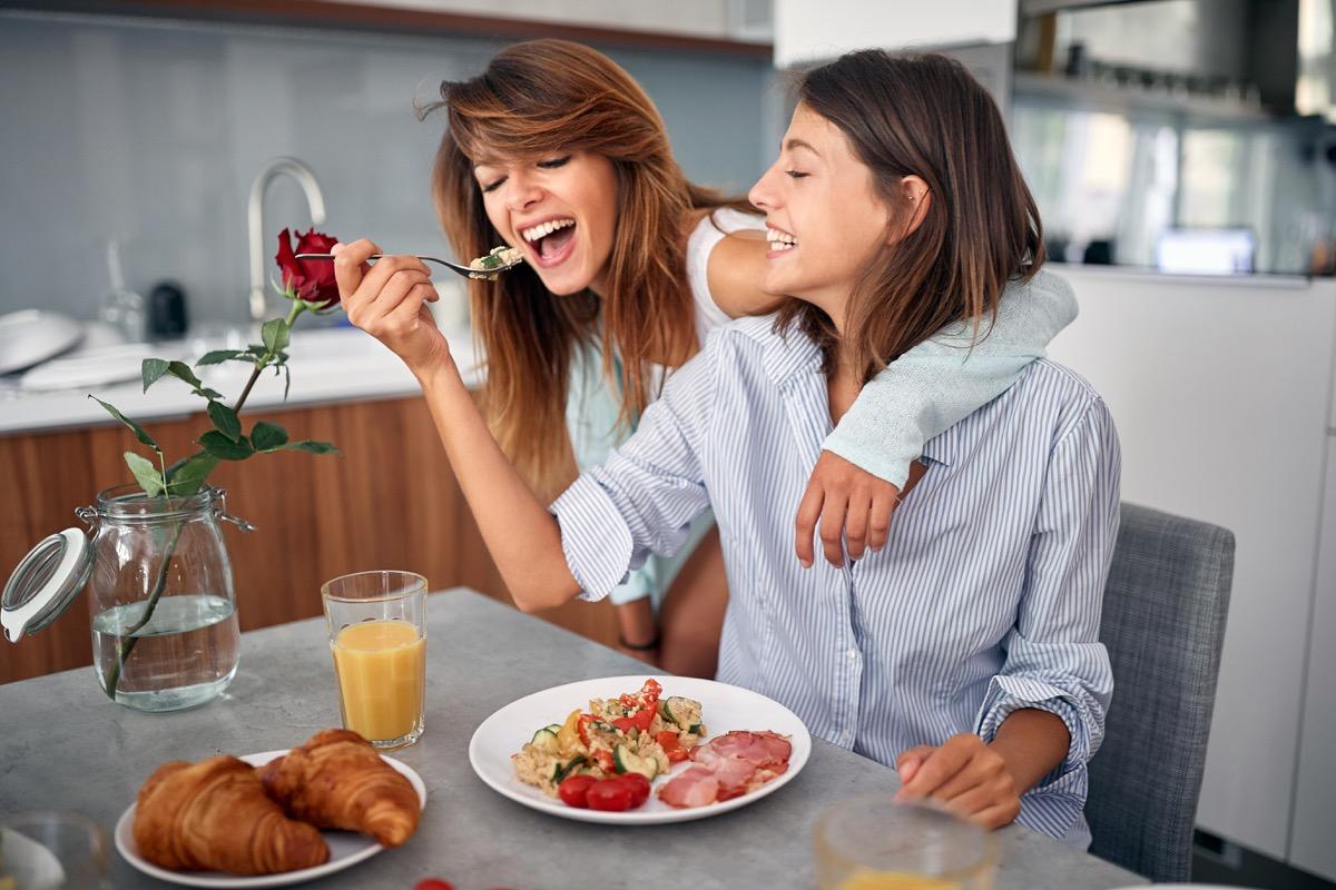 white woman feeding her girlfriend breakfast