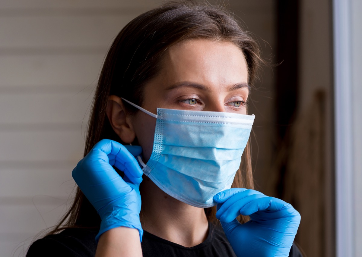 white woman putting on face mask and gloves