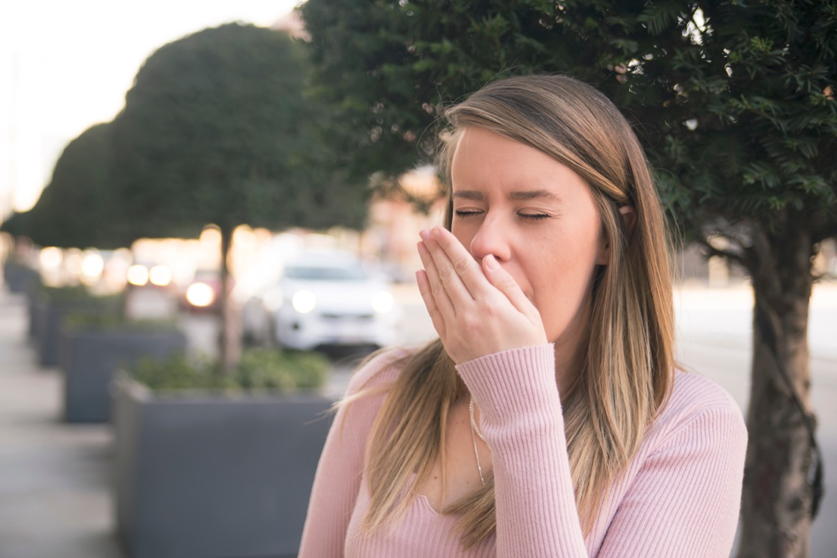 white woman sneezing into hand outdoors