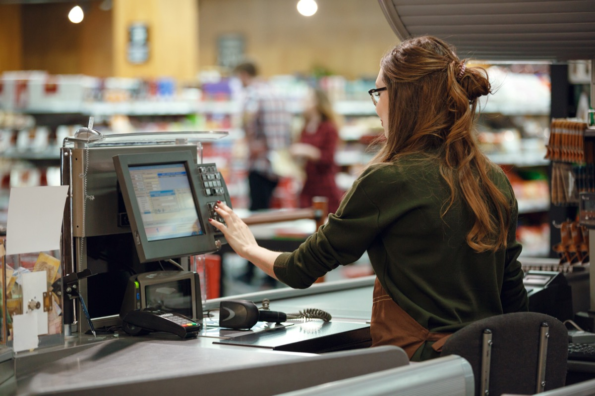 young white woman operating cash register at grocery store