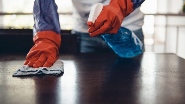 Cropped shot of a man cleaning a kitchen counter at home