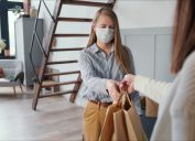 white woman accepting delivery wearing mask