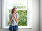 happy woman standing in front of open window