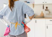 woman holding hands on hips looking at kitchen getting ready to clean her house
