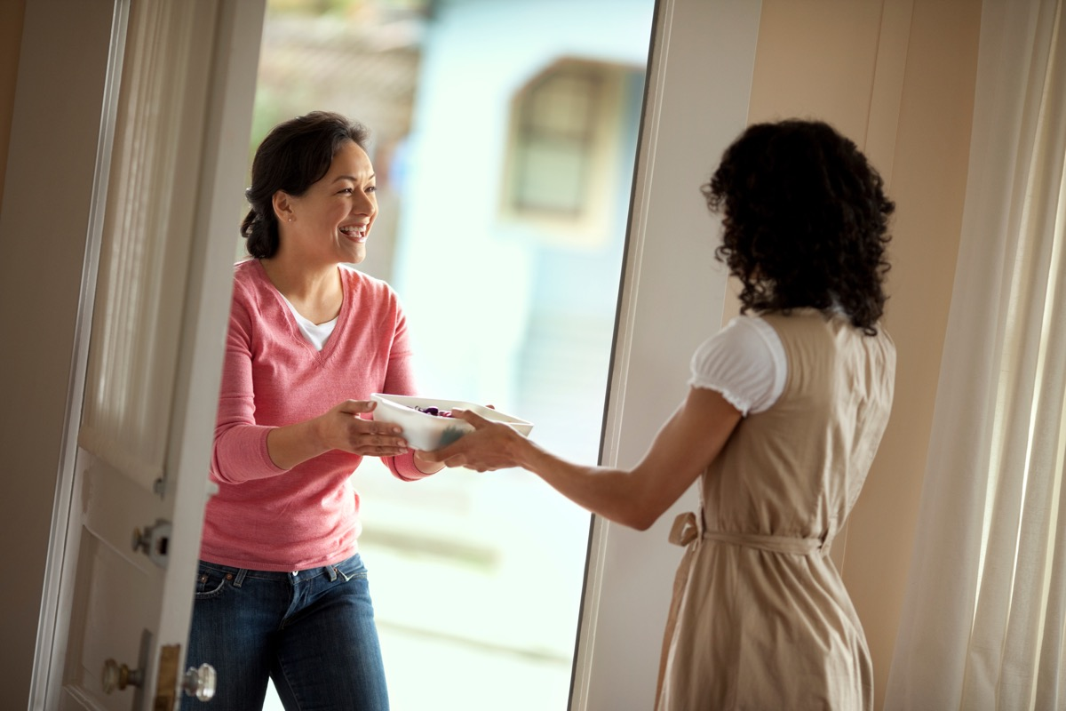 woman delivering casserole dish to friend
