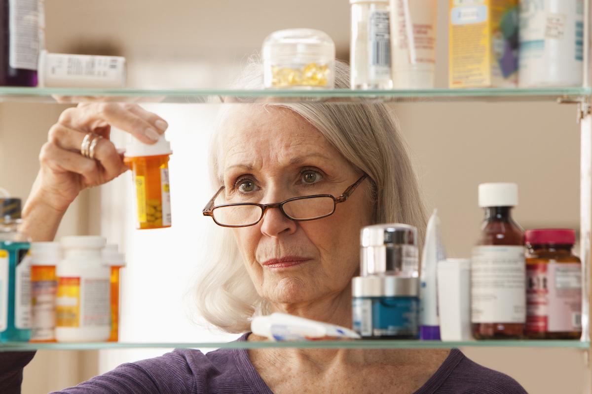 Senior woman looking at prescription bottles