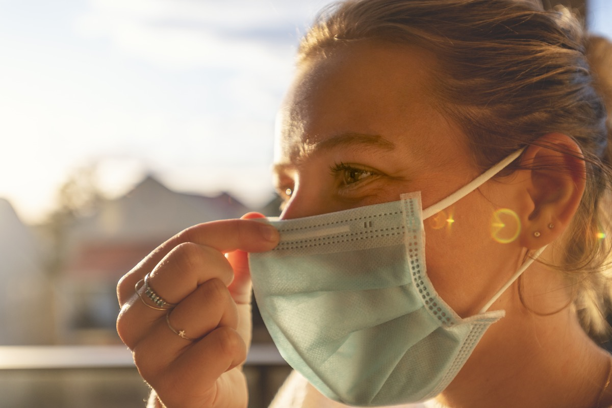 Woman putting on a surgical face mask. She is applying it to her face and is adjusting the mask for a proper fit. Back lit at sunset.