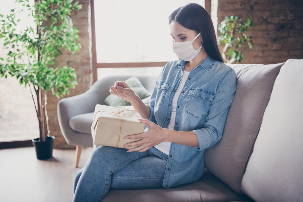 woman wearing mask opening package on couch inside home