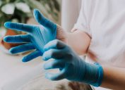 person wearing her latex surgical gloves at home before the cleaning process