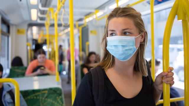 woman wearing disposable mask on public transportation during coronavirus pandemic