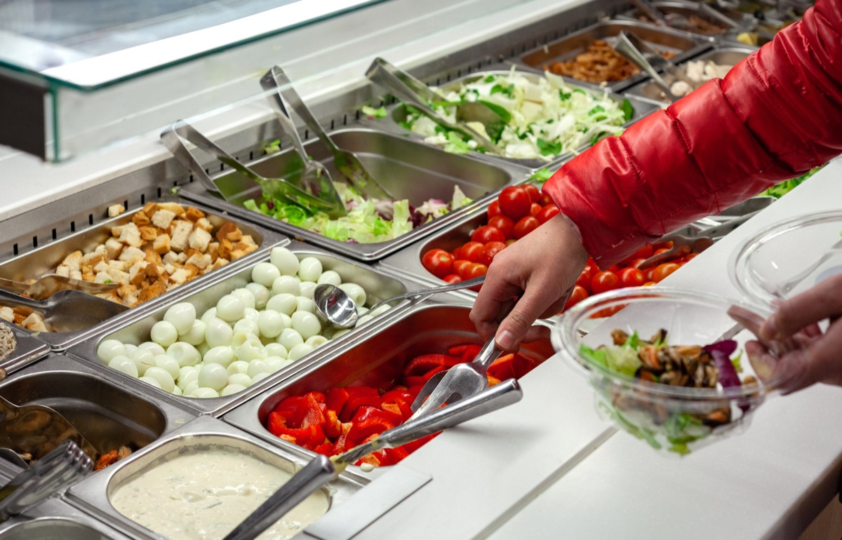 hand reaching into salad bar container