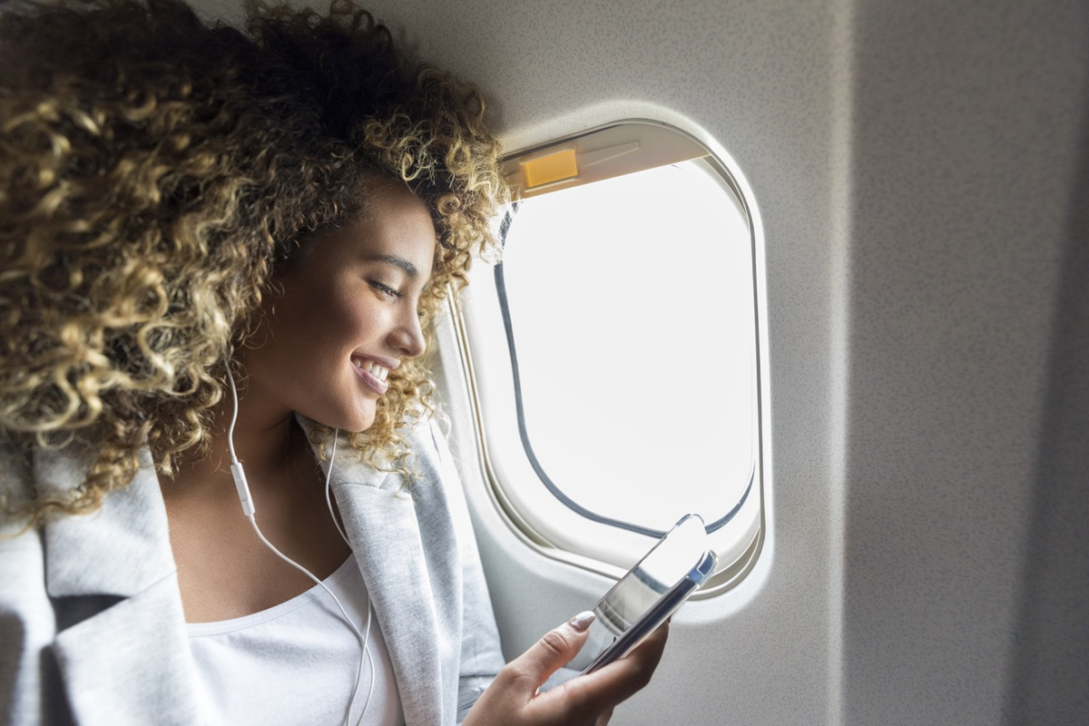 Confident woman selects music on smartphone to listen to during her flight. She is smiling cheerfully while wearing earbuds.
