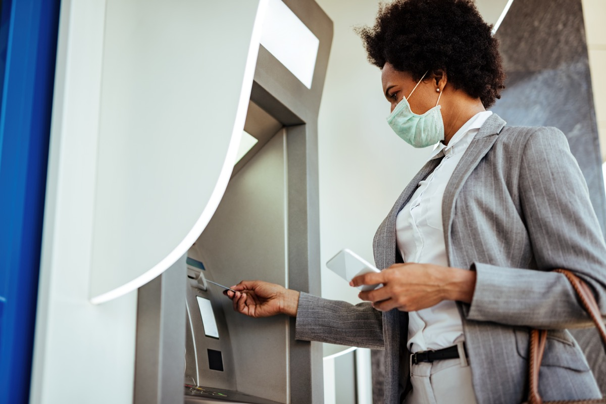 Low angle view of businesswoman inserting credit card and withdrawing cash at ATM while wearing protective mask on her face.