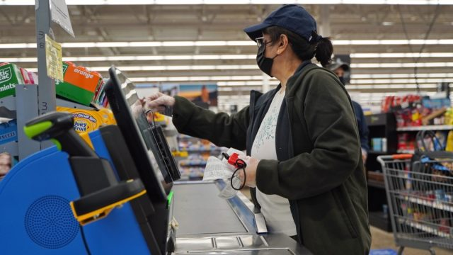 woman wearing mask and gloves at walmart checkout