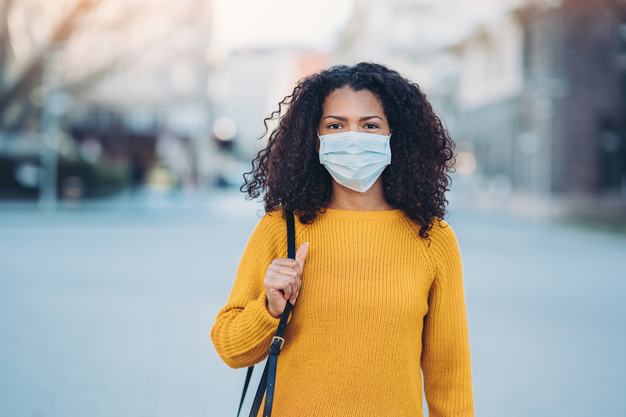 a young woman in a yellow sweater wearing a surgical mask