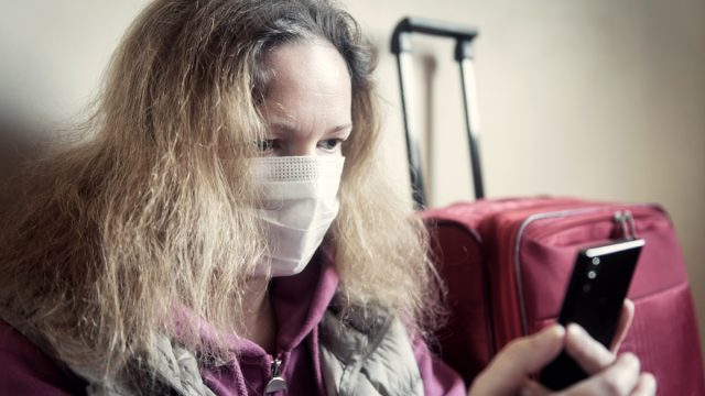 woman looking at smartphone sitting next to suitcase