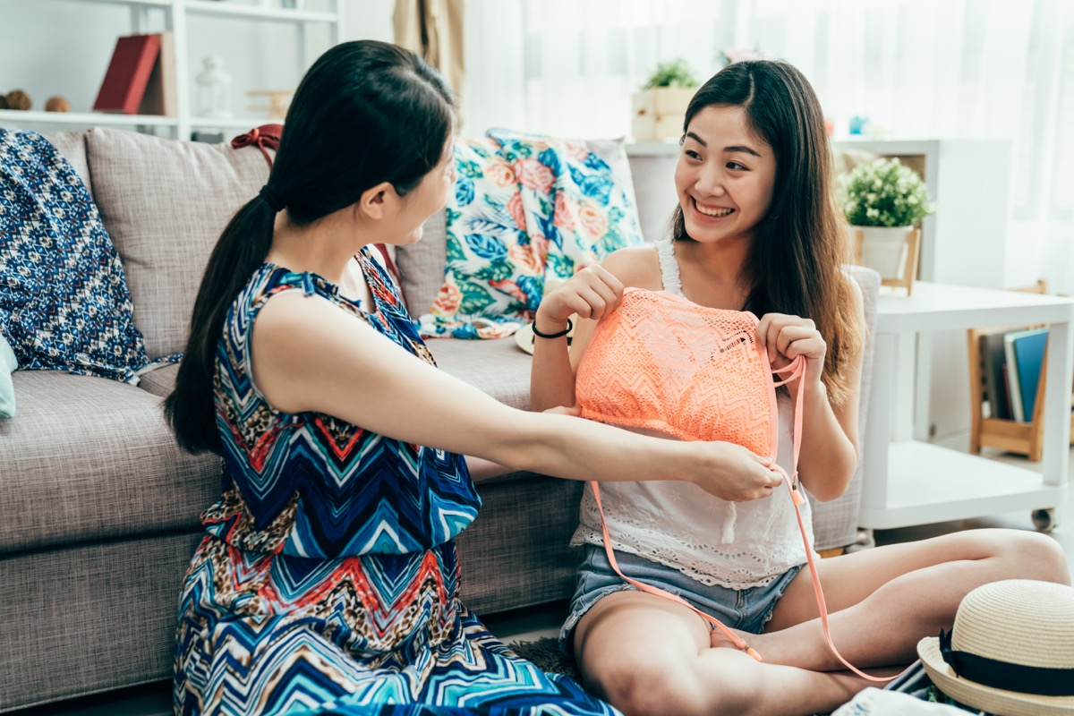 two young asian women sharing clothes