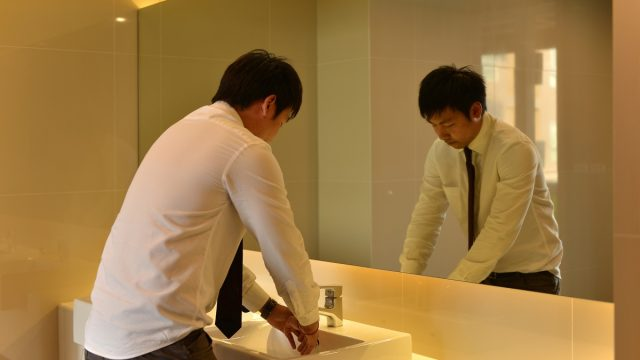 young asian man washing hands in public bathroom