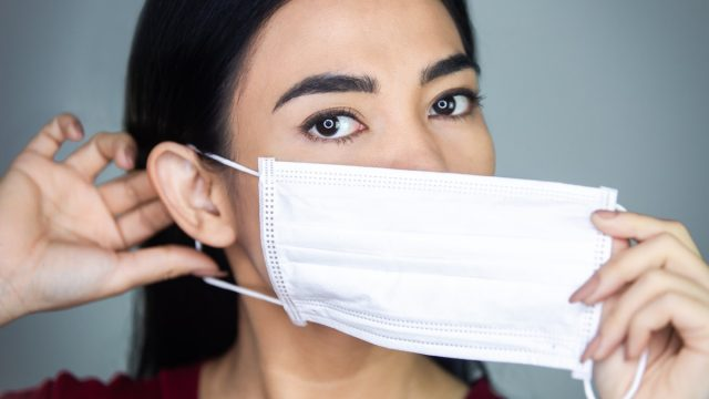 young asian woman putting on face mask