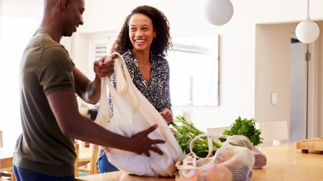 Young black couple unpacking groceries