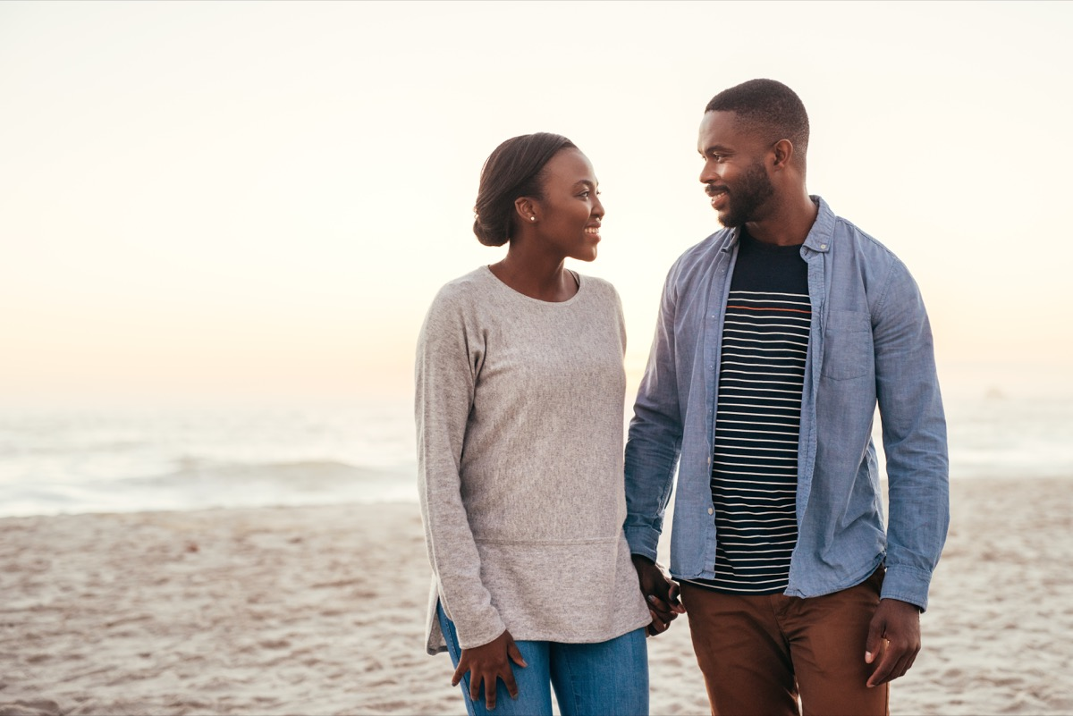 young black couple walking on beach