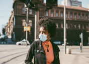 Young black woman standing on city street with protective mask on her face