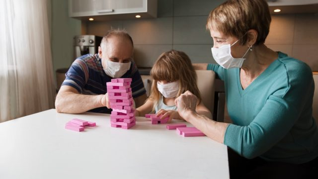 young white girl playing jumbling tower game with older adults