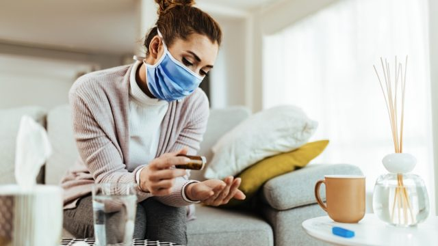 young woman taking pill while wearing face mask