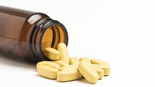 Vitamin pills spilling from an open bottle