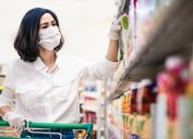 Asian woman wearing mask and gloves in grocery store