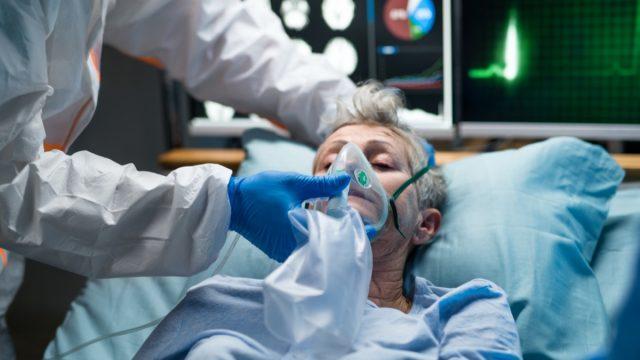 Senior female coronavirus patient in hospital bed
