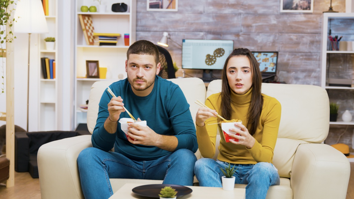 Couple sitting on couch and eating Chinese food