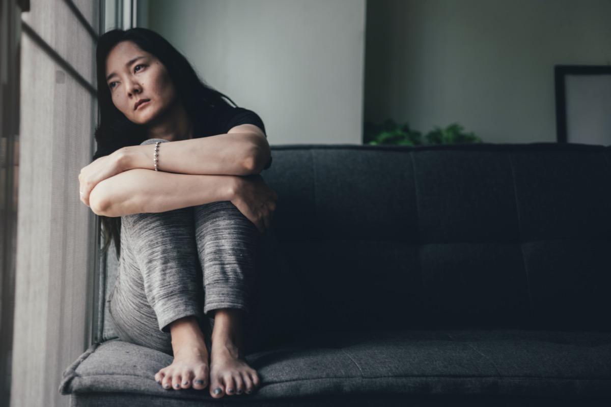 Depressed woman leaning against window