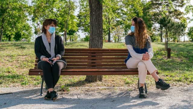 Mom and daughter social distancing on park bench