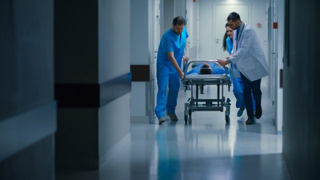 Doctors moving patient in gurney
